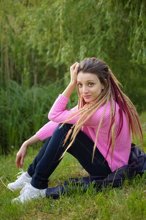 Outdoors female portrait of a modern girl with dreadlocks wearing pink sweater and dark jeans in a city park during a sunset, be free, be youself concept Archivio Fotografico