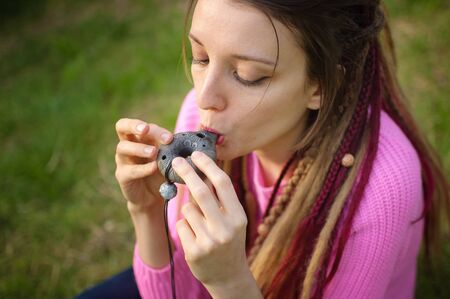 Portrait of young female shaman in pink knitted sweater playing on ceramic ocarina in the forest during autumn or spring. Relaxing tranquil scene, traditional music concepts