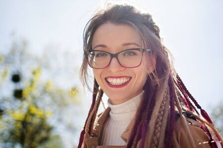 Young girl with long dreadlocks and eyeglasses in nude color trench is looking at the camera with charming smile on sky background. Positive psychology concept Archivio Fotografico