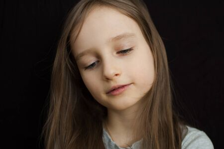 Portrait of a little sad girl with long blond hair and closed eyes on black background in studio Archivio Fotografico