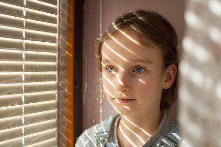 Portrait of a little girl with long blond hair and blue eyes is sitting near the window with blinds during sunny day at home