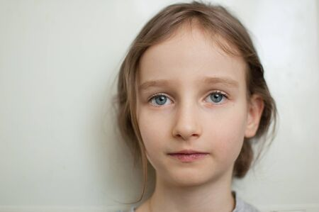 Portrait of a little girl with long blond hair and blue eyes with ponytail is standing on white background in studio Archivio Fotografico