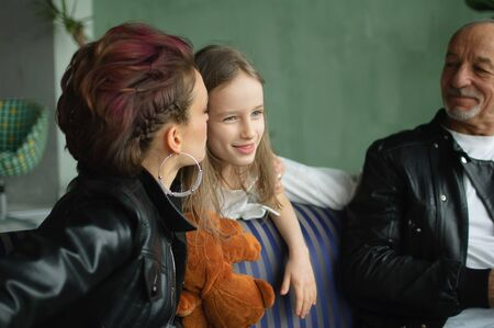 Family portrait of adult daughter, little granddaughter and senior grandfather in loft room with houseplants. Man and woman are wearing black leather jackets in punk style, generation concept