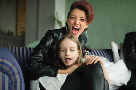 Crazy mother in black leather jaket and pants hugging her little daughter in white dress, they are looking at the camera with opened mouths and grimacing in loft room with houseplants. Archivio Fotografico