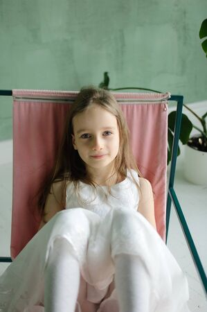 Cute kid girl 5-7 year old sitting on chair in loft style room. Birthday celebration, party concepts Archivio Fotografico