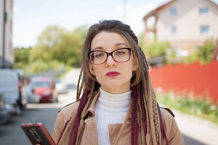 Modern young business woman with long dreadlocks and eyeglasses is talking with the client by mobile phone standing at the street near the buildings.
