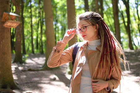Young woman wearing glasses, casual nude trench, and dreadlocks is standing at the urban park on trees background during sunny spring day outdoors Archivio Fotografico