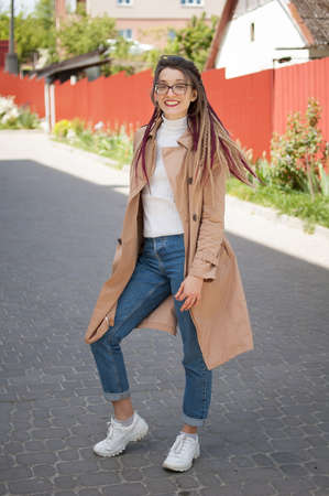 Full height portrait of young woman wearing glasses, casual nude trench, jeans and dreadlocks standing at the street on buildings background during sunny spring day outdoors