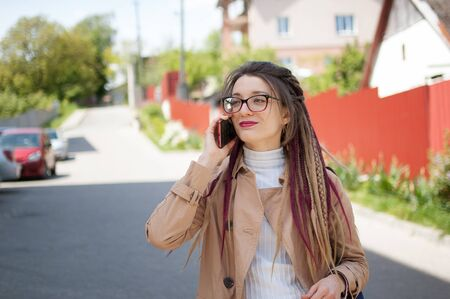 Modern young business woman with long dreadlocks and eyeglasses is talking with the client by mobile phone standing at the street near the buildings Archivio Fotografico