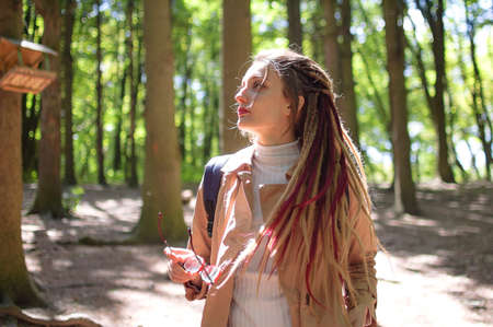 Young woman wearing glasses, casual trench, and dreadlocks is standing at the urban park on trees background during sunny spring day outdoors Archivio Fotografico