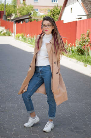 Full height portrait of young woman wearing glasses, casual trench, jeans and dreadlocks standing at the street on buildings background during sunny spring day outdoors Archivio Fotografico