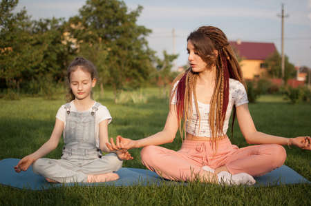 Young mother with dreadlocks and little daughter are doing yoga exercises in lotus position on grass in the park at the day time. Concept of friendly family and of summer vacation.