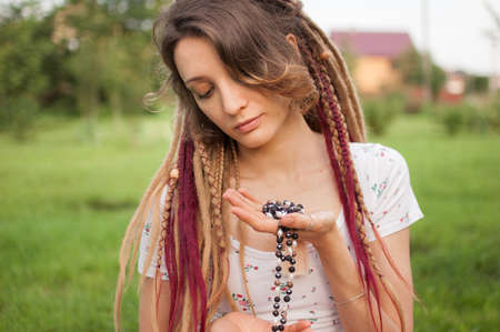Young beautiful girl with long dreadlocks holds in hands the necklace made by natural stones for meditation outdoors during morning on green grass of her backyard Archivio Fotografico