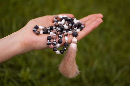 Female hand holding a buddhist japa mala made from 108 natural stones beads for meditation on green grass background
