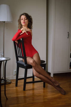 Portrait of attractive brown-haired woman in red bodysuit underwear sitting on dark brown chair. Sensual stylish image of a girl with long legs in stockings