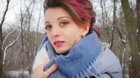 Attractive young woman with perfect skin and makeup with dark pink hair is possing on winter park background wearing blue scarf and silver earrings