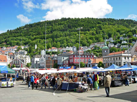 Bergen, Norway - June 5, 2009: People shop at the market in Bergen Norway. At many of the market stalls fresh fish and seafood are offered. But there are so sold fruits, vegetables, handicrafts and souvenirs. Editorial