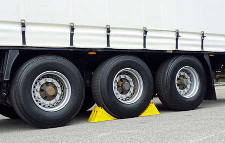 chock: Yellow chocks at the wheel of a truck-trailer