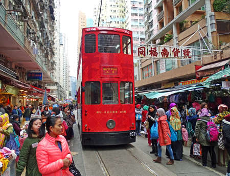 streetlife: Hong Kong, China - February 10, 2016: A red double-storey-tram runs through a market in Hong Kong, North Point district. Many people go shopping in nearby stores. The people come to the moving tram very close.
