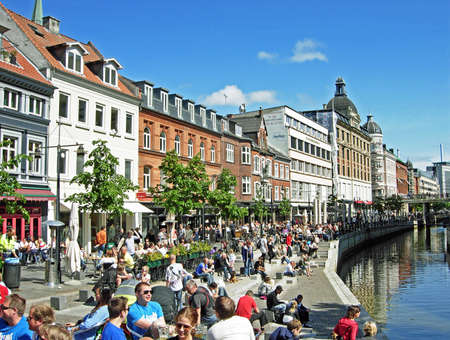 Aarhus, Denmark - June 6, 2009: Many people enjoying a sunny day at Aboulevard, the promenade along the river Aarhus A. Aarhus is located in the region Midtjylland and with about 260,000 inhabitants, the second large largest city in Denmark.
