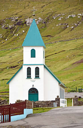 mountainside: Small church in the village of Gjogv on the Faroe Islands in front of a mountainside