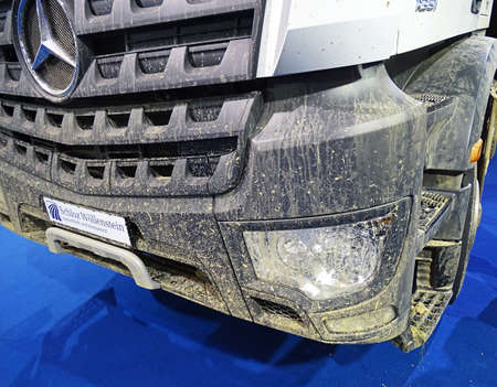 front end: Chemnitz, Germany - October 4, 2015: Muddy front end of a truck of the type Mercedes-Benz Arocs 1851 with the typical Mercedes star. Mercedes-Benz is a trademark of vehicles of Daimler AG.