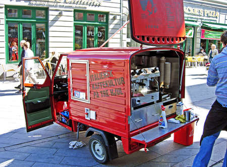 espresso machine: Aarhus, Denmark - June 6, 2009: A man sells coffee specialties in a pedestrian area of ??downtown of Aarhus in Denmark. The espresso machine is installed in a little red tricycle Italian car.