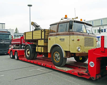 rt: Chemnitz, Germany - October 4, 2015: A historic Skoda truck of the type 706 RT is loaded on a modern low loader. The loader is parked in a parking lot in Chemnitz (Germany). The Skoda 706 RT was a truck of the Czechoslovak commercial vehicle manufacturer  Editorial