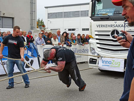 forceful: Chemnitz, Germany - October 4, 2015: A strong man pulls a 15 ton heavy truck with a rope in the final of FIROCON Truck Pull European Championships. The referee Observed the competition with a stopwatch in hand. A one assist the athlete, by holding the rop