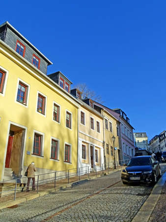 erzgebirge: Annaberg-Buchholz, Germany - December 20, 2015: A woman walking up a steep road in the old town of Annaberg-Buchholz (Germany) along beautifully restored houses.