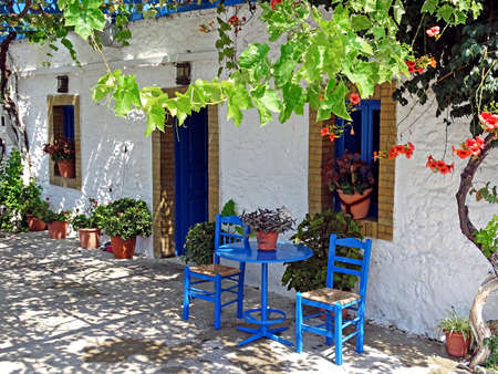 Kos, Greece - July 31, 2015: House in Kos with in the typical for Greece blue-painted furniture in front of it. Many tourists come to Greece to see examined idyllic places. For the small Iceland of Kos tourism is the main source of income. It is feared di