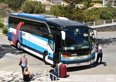 greatly: Hersonissos, Greece - July 22, 2016: Two women waiting in Hersonissos on the arrival of the shuttle bus to the airport. Their luggage is already ready for loading. In 2016 the Greek tourism industry has benefited greatly from the decline in bookings in Ne