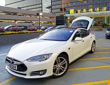booked: Chek Lap Kok, Hong Kong - February 8, 2016: An electric vehicle model S of the brand Tesla Motors parked at the airport at Chek Lap Kok, Hong Kong. The driver loads the luggage of passengers in the trunk, who booked the car for airport transfer. In the ba Editorial