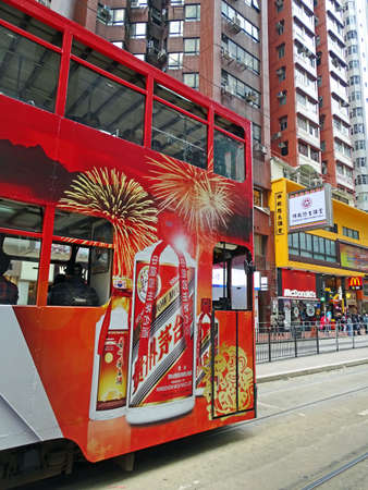 Hong Kong, China - February 10, 2016: A red double-storey-tram runs on the Kings Road in Hong Kongs North Point district. People waiting on the sidewalk in front of a branch of McDonalds. The tram in the north of the Hong Kong Iceland which established