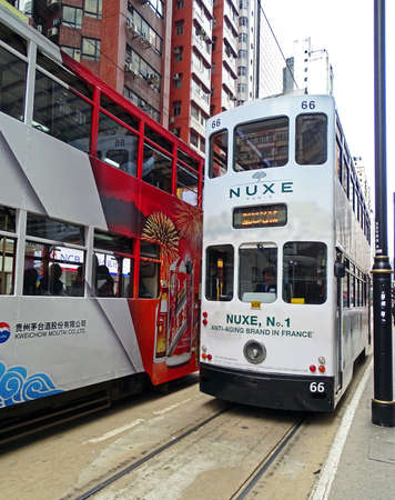 North Point, Hong Kong - February 10, 2016: Two old double-decker trams encounter whileDriving through North Point, Hong Kong. Both trams are covered with advertising. The tram in the north of the Hong Kong Iceland which established in 1904. The only doub