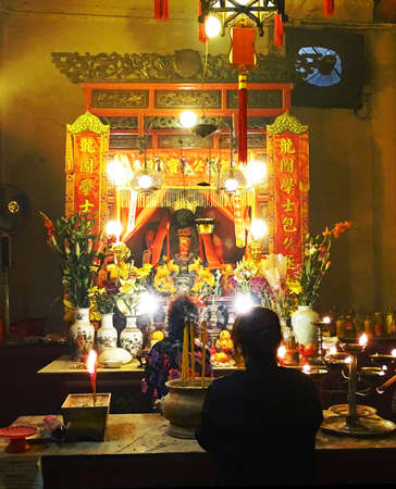 Sheung Wan, Hong Kong - February 10, 2016: Two women pray at on altar inside the Man Mo Temple in Sheung Wan, Hong Kong. On the altar are incense sticks, candles, flowers and oranges. The temple which built in 1847 and is dedicated to the gods Man Cheong  Editorial