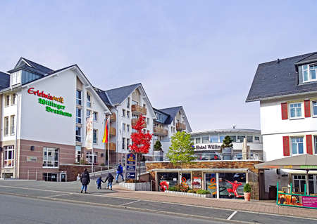Willingen, Germany - October 12, 2015: Two adults and two children walking in Willingen from the main road to the Best Western Hotel. In the hotel complex is located so the world of experience Willinger Brauhaus with its own brewery. Willingen is a very