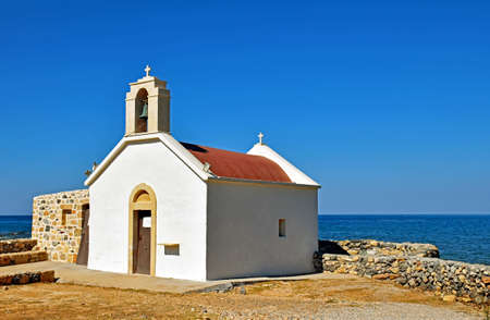Small church by the sea in Hersonissos on the Iceland of Crete, Greece Stock Photo