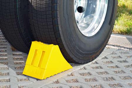 주차 된 트럭의 바퀴에서 노란색 쐐기 스톡 콘텐츠