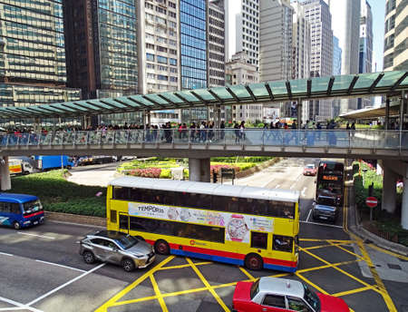 Central, Hong Kong - February 09, 2016: Traffic between high-rise buildings during the rush hour in the Central District on Hong Kong Iceland. Many people walk on a pedestrian bridge over a road crossing All which is driven by cars and buses.