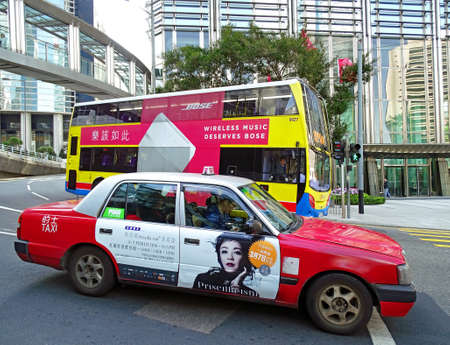 Central, Hong Kong - February 09, 2016: A red Toyota Comfort taxi and a yellow double-decker bus from the city bus company run along a street in the Central district next to eachother. Editorial