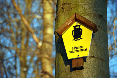 On a tree attached yellow sign with the lettering Areas Natural Monument in German language