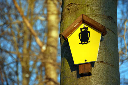 On a tree attached yellow sign which means natural monument area Stock Photo