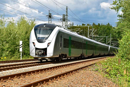 A modern electric regional train runs on a multi-lane track through natural surroundings Stock Photo