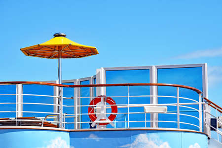 Sun deck with umbrella, sunbeds and rescue ring on a cruise ship