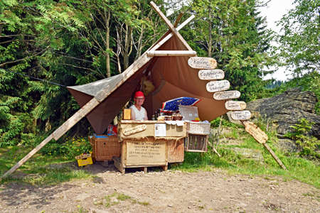 Pobershau, Germany - June 25, 2016: A man with the nickname Coffee-Kurt sells at his stall in the middle of the forest self-grinded coffee and homemade cake. Its sales stand is very popular with hikers in the Saxon Erzgebirge in Germany. Editorial