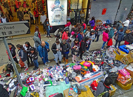Wan Chai, Hong Kong - February 10, 2016: People are shopping in an improvised market on the footpath of Johnston Road in Hong Kong. The goods are messy on the floor.