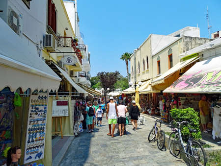Kos, Greece - July 31, 2015: Tourists strolling for shopping and sightseeing on a street in Kos town on the island of Kos in Greece.