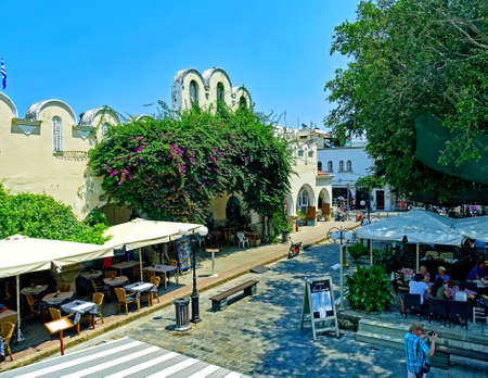 Kos, Greece - July 31, 2015: People enjoying a sunny summer day at outdoor restaurants at the old town of Kos Town on the island of Kos in Greece.