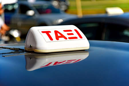 Taxi sign in Greek language on the shiny roof of a car